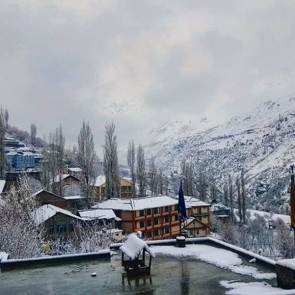 The snow capped mountains and houses at Manali